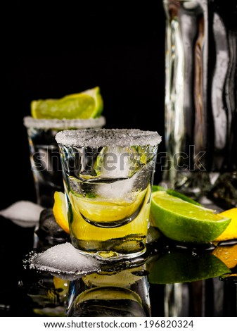 Tequila with lemon or lime and salt on reflex background - stock photo