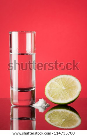 Tequila with lime and salt on a red background - stock photo