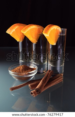 tequila with orange and cinnamon on a glass table. - stock photo