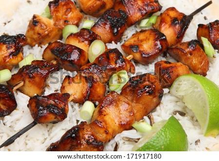 Teriyaki chicken kebabs with rice. - stock photo