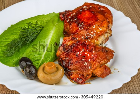 Teriyaki sauce chicken thights with sesame seeds on wood background