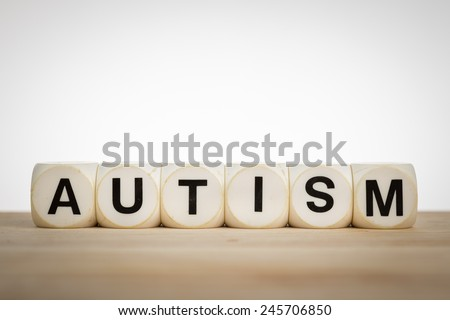 Term Autism spelled out with toy dice on a board - stock photo