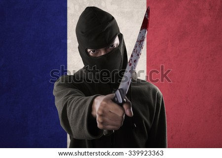 Terorrism concept: terrorist threatening with a knife in front of France national flag