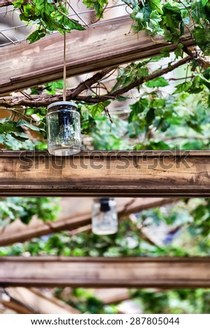 Terrace having a lightning system made by used glass jars as lamps - stock photo