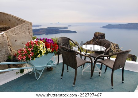 Terrace in Greece with view of Aegean sea, decorated with flower cart