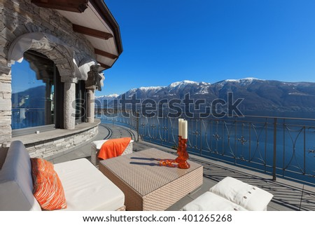 Terrace lounge with comfortable divan and lake view in a luxury house - stock photo