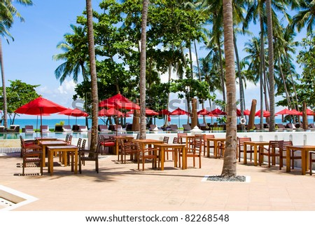 Terrace of a restaurant with red sun shades on a beautiful beach - stock photo