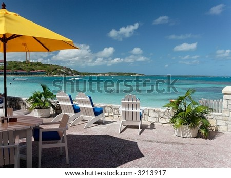 Terrace of a restaurant with yello sun shades on a beautiful caribbean beach - stock photo