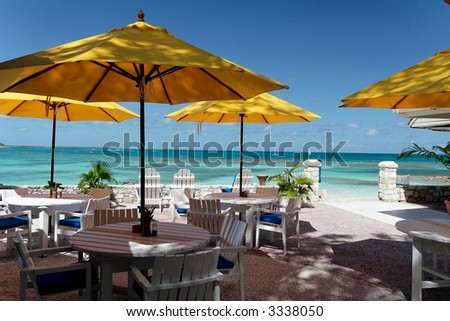 Terrace of a restaurant with yello sun shades on a beautiful caribbean beach