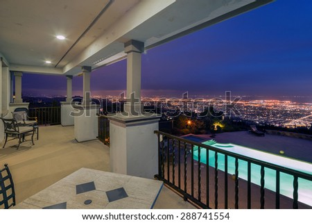 Terrace of Mediterranean home with pool and garden with city skyline at summer time. - stock photo