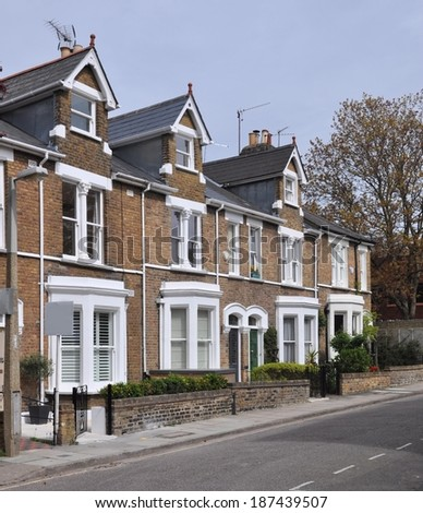 Terrace of 19th century English Victorian period town houses, with blank sales signboard.