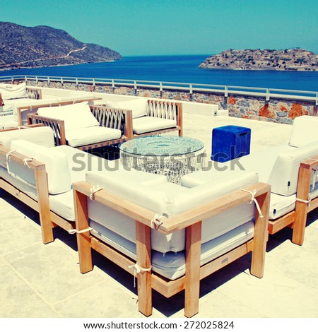 Terrace sea view with outdoor lounge furniture in a luxury resort, Crete, Greece. Square toned image, instagram effect - stock photo