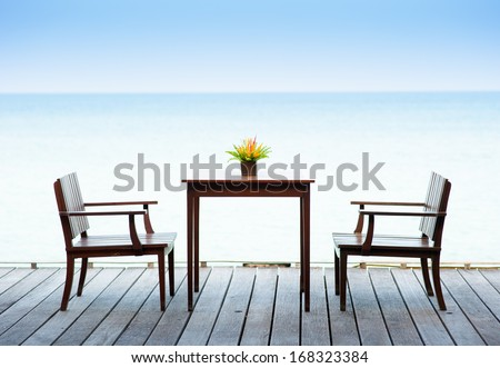 Terrace sea view with outdoor wood chairs and table - stock photo
