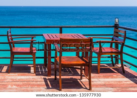 Terrace sea view with outdoor wood chairs and table in a luxury resort - stock photo