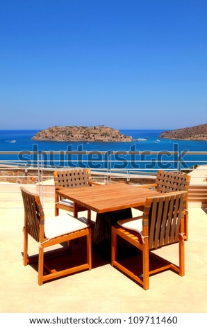 Terrace sea view with outdoor wood chairs and table in a luxury resort(Crete, Greece) - stock photo