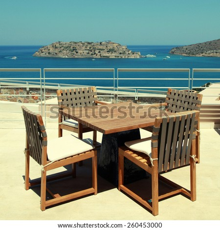 Terrace seaview with outdoor wood chairs and table in a luxury resort(Crete, Greece). Square toned image, instagram effect - stock photo