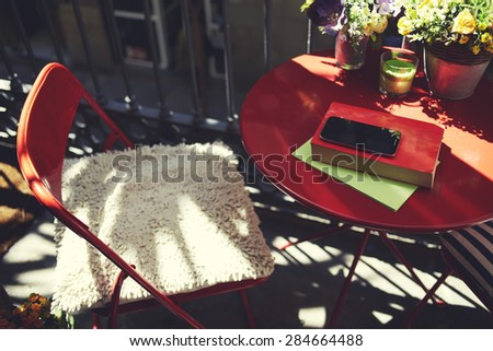 Terrace table with book and mobile phone at sunny beautiful day, empty chair at table with colorful flowers, novel and smart phone lying, recreation time at home, inspiration for writer,filtered image - stock photo