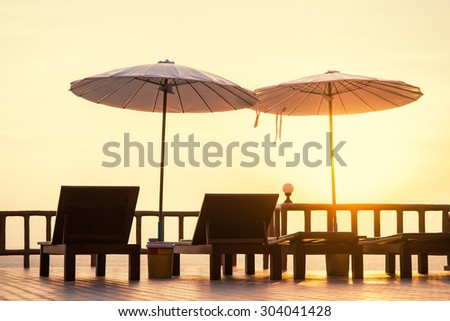 Terrace with a view on sea and sunset. Umbrellas and lounge chair in a sunlight.  - stock photo