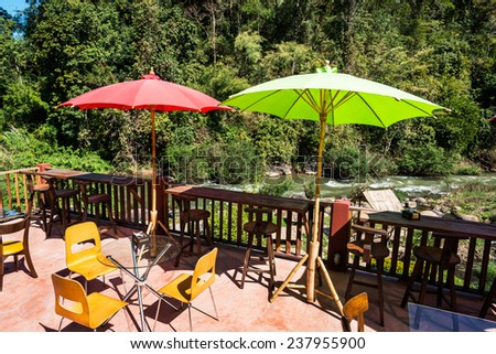 Terrace with parasol and chairs with view on river and mountains  - stock photo