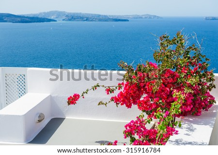 Terrace with red flowers. Santorini island, Greece. Beautiful landscape with sea view. - stock photo