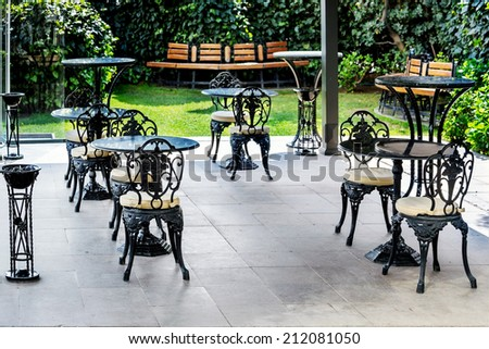Terrace with vintage tables and chairs in a cafe or restaurant under a canopy in a beautiful garden - stock photo