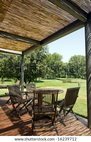 Terrace with wooden table and chairs under shelter of straw. Looking over golf course