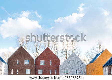 Terraced houses with minimalist design and different colors with classic gabled roof - stock photo