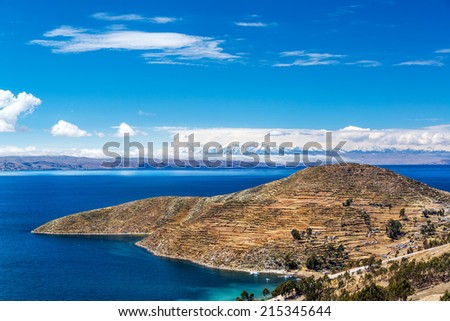 Terraced landscape of Isla del Sol with Andes mountains in the background on the Bolivian side of Lake Titicaca - stock photo