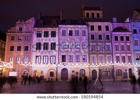 Terraced tenement houses at night in the Old Town of Warsaw, Poland, Christmas illumination. - stock photo