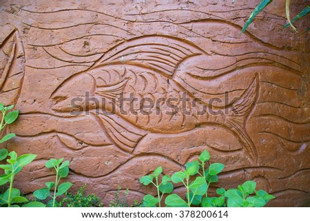Terracotta art/ Tribal art, picture of a fish in ocean/ sea/ lake/ pond/ water. Carved image in terracotta in a park with lush green plants in  Wayanad,India. Fremont indian culture petroglyph - stock photo