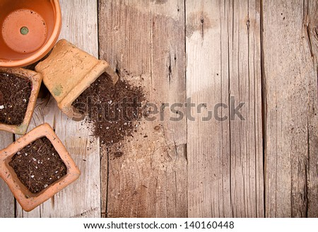Terracotta or clay gardening pots with dirt spilling out of a pot, on a wooden background - stock photo