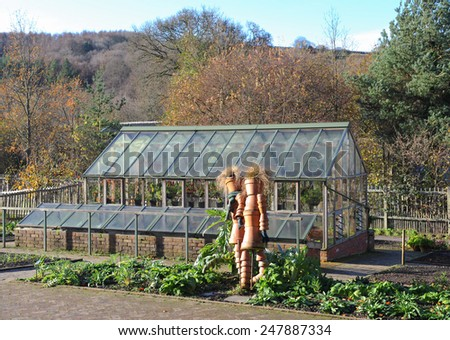 Terracotta Scarecrows in front of a Greenhouse in the Fruit and Vegetable Garden at Rosemoor, near Bideford, Devon, England, UK - stock photo