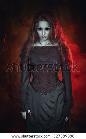 Terrible beautiful halloween witch with long hair in the hell - stock photo
