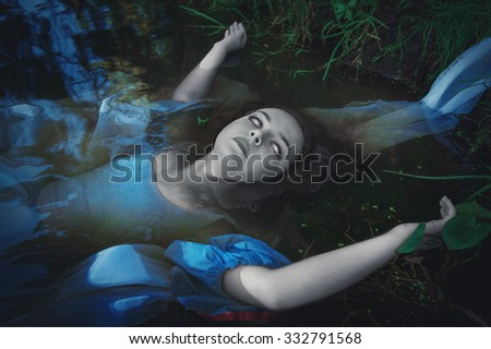 Terrible dead ghost woman lying in the water  - stock photo