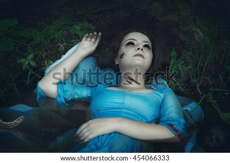 Terrible drowned dead ghost woman lying in the water