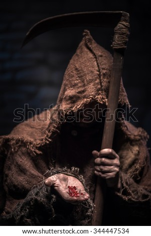 Terrible epitome of death is holding narcotic red bolus. He is standing and looking at it seriously. The man is standing and holding a scythe - stock photo