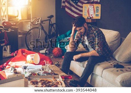 Terrible hangover. Frustrated young man keeping hand in hair while sitting on sofa in messy room after party - stock photo