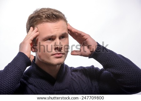 Terrible headache. Young handsome man in cardigan touching his head and looking away while standing against white background - stock photo
