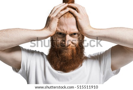 Terrible headache. Young man in shirt touching his head and keeping eyes open while standing against white background. Bad life concept. Close up portrait.