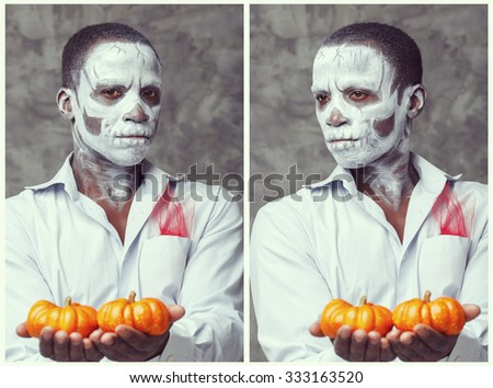 Terrible man. Human white skeleton holding two pumpkins in his hands. Symbol of the holiday Halloween. Skull. African witch man. Zombie. Halloween mask. Scary dress for a party on Halloween. Poster. - stock photo