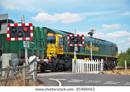 TERRICK,ENGLAND- JULY 14: A London waste Freightliner train passes over a level crossing on July 14, 2011 at Terrick. Ninety-five percent of UK accidents at level crossings are due to pedestrian or auto driver misuse - stock photo