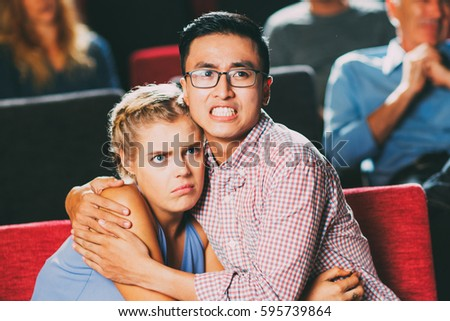 Terrified couple watching horror movie in cinema