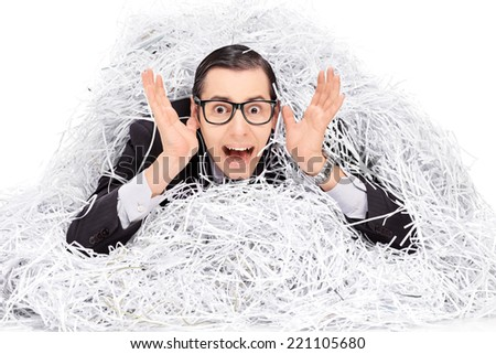 Terrified man covered in a pile of shredder paper isolated on white background - stock photo