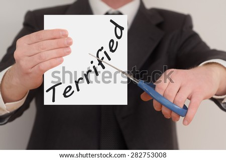 Terrified, man in suit cutting text on paper with scissors