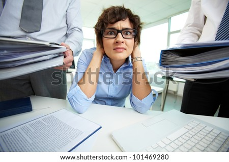 Terrified secretary touching her head while looking at camera surrounded by big heaps of papers