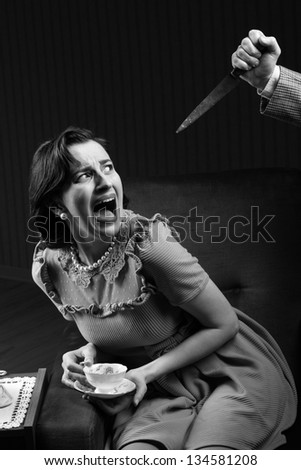 Terrified woman by a man murderess with a knife. Classic film noir style - stock photo