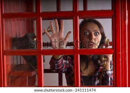 Terrified woman trapped in a telephone booth staring out with a wild wide eyed expression of panic as she holds the vintage handset in her hand - stock photo