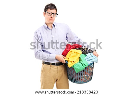 Terrified young man holding a laundry basket full of clothes isolated on white background - stock photo