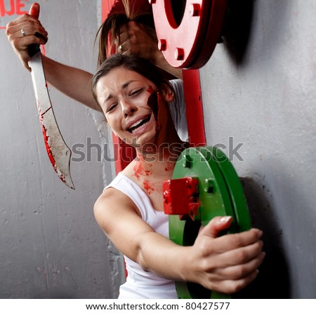 Terrified young woman clinging on for her life. A machete killer is about to kill her. Torture series. - stock photo