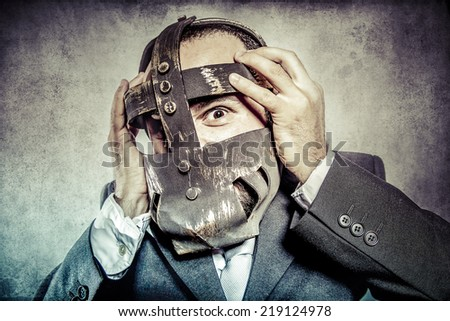 terror, business man with iron mask - stock photo